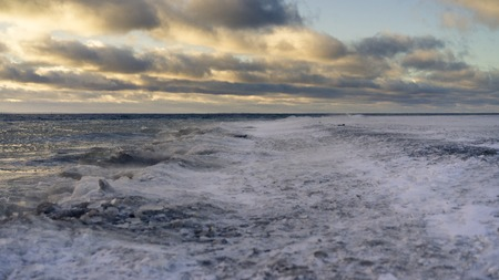 Beach is covered by dark light. Surface of beach is covered by snow and ice. Dark clouds run on sky. Waves are fallen down on a surface. Cold temperature and strong wind in air.