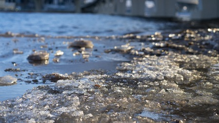 Close up picture of beachs surface. Ice is melted. Sand is wet and dirty. Some sun lights reflects on melted surface of ice cover.