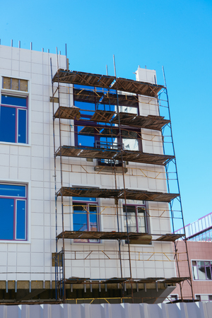 Scaffoldings stay close to a wall of building with unfinished part of rainscreen system for a insulation of building wall.