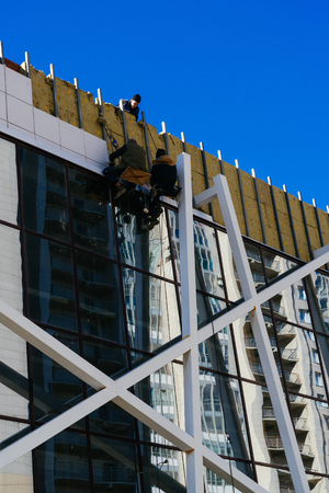 Few workers are installing heat insulation material for a facade of building. Men are using ropes for a safe high-altitude works. People installing rainscreen system for a insulation of building wall. Stok Fotoğraf
