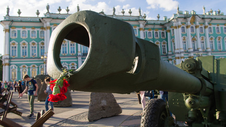 Saint-Petersburg. Russian Federation. 9 August 2017. The background is the Palace square in Day of memory and grief. A cannon 122 mm. USSR weapon . A flower of red carnation inside of barrel. Editöryel