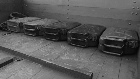 Old metal gas canisters lay down on a wood surface of cars trunk. Canisters are used in world war 2 in USSR soviet union. Black and white.