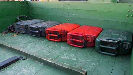 Old metal red and green gas canisters lay down on a wood surface of cars trunk. Canisters are used in world war 2 in USSR soviet union. Stok Fotoğraf