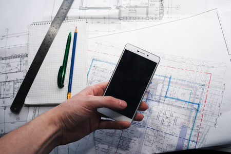 Green pen, blue pencil, white cellphone, metal ruler, notepad and some paper draws of a house (home) are laying down on white table. All staff is for a architecture negotiation. A mens hand is holding a cellphone. Stok Fotoğraf