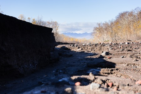 Road after mudflow. A lot of huge stones and dirt are everywhere. Blue sy and trees are around. Russia Autumn 2017 Kamchatka.