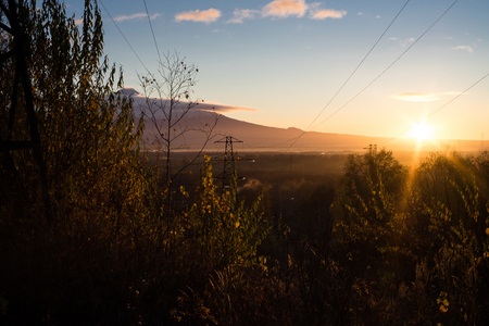 Sunrise is during great morning in mountains. Beautiful grass and trees are under warm light. Sky is highlighted by the sun. Golden autumn in mountains.