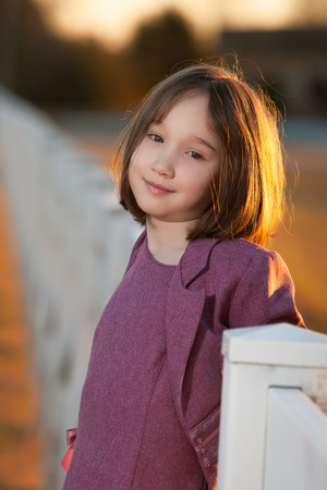 A beautiful young girl smiling at the camera while standing on a fence at sunset.