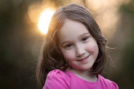 A beautiful young girl looking at the camera while the sun sets in the background.