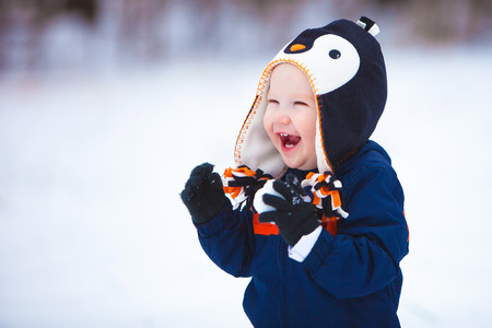 A young boy wearing a winter coat and hat laughs as he plays in the snow. Stock Photo