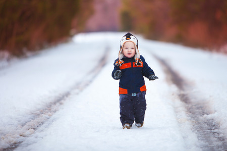 A young boy wearing a winter coat and had smiles as he walks down a snow covered road.