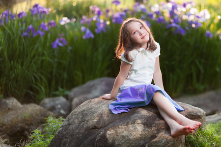 A beautiful young girl sits on a rock in a garden, deep in wistful thought.