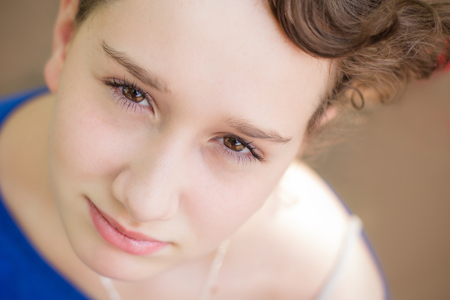 eyes looking up: Gorgeous young girl with stunning eyes looking up at the camera. Stock Photo