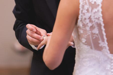 Groom placing wedding band on brides finger