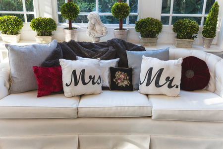 señora: Mr and Mrs pillows on a couch at a wedding reception