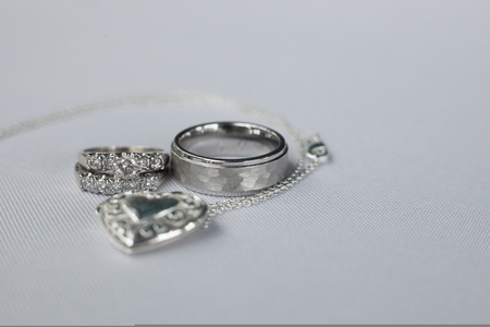 Wedding rings on white with a locket