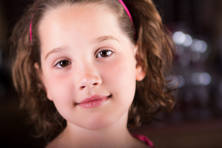 Beautiful young girl looking peacefully at the camera Фото со стока