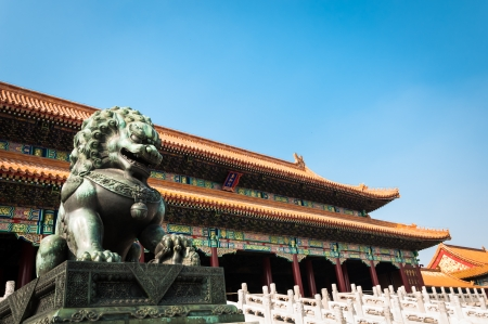 A bronze lion statue stands guard at the Forbidden City  photo