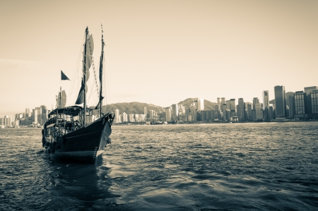 A traditional junk ship sails along Victoria Harbor in Hong Kong  photo