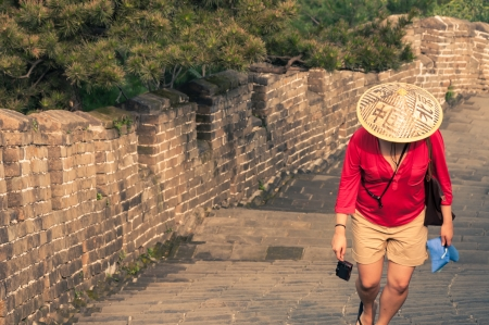 A young woman climbs the arduous steps of the Great Wall of China  photo