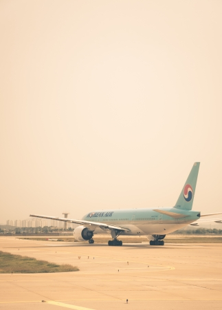 A Korean Air plane taxis along the runway, getting ready for takeoff.