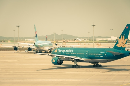 A Vietnam Airlines plane taxis along the runway, getting ready for takeoff.