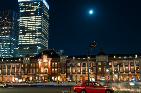 Tokyo Station at night, with the blurred motion of pedestrians and traffic.