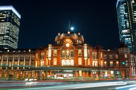 Tokyo Station at night, with the blurred motion of pedestrians and traffic. photo