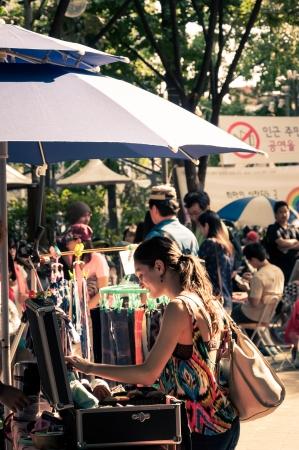 Een jonge vrouw kijkt over enkele sjaals op een rommelmarkt in Hongdae Redactioneel