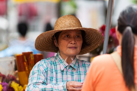 market vendor: A woman sells flowers at a market in Singapore