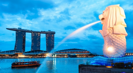 The Merlion fountain lit up at night in Singapore.