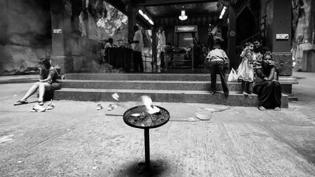 hindues: Hindúes y turistas se sientan en las escaleras fuera del pequeño templo hindú dentro de las Cuevas Batu el 27 de diciembre de 2013, de Kuala Lumpur, Malasia