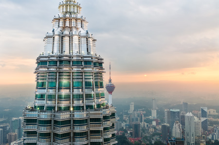 kuala lumpur: The setting sun gleams off of the second Petronas Tower and KL Tower in the distance  Photo taken December 26, 2013 in Kuala Lumpur, Malaysia  Editorial