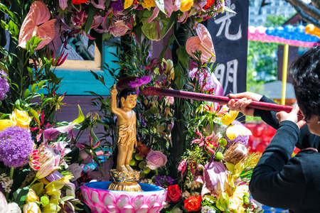 A Buddhist woman pours water over a small Buddha statue at Jogyesa Temple on May 5, 2014 in Seoul, South Korea.