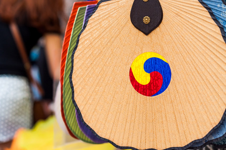 A fan painted with a traditional Korean symbol hangs outside a vendor in the Insadong district of Seoul, South Korea.