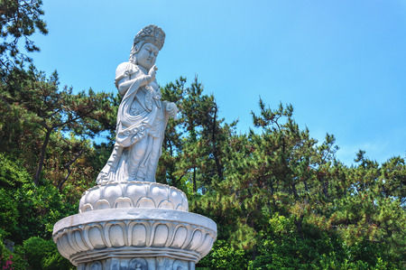 A stone Buddha overlooks the east sea from atop Haedong Yonggungsa Temple in Busan, South Korea  photo
