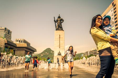 Mensen spelen in de fonteinen van Gwanghwamun plein in Seoul, Zuid-Korea Redactioneel