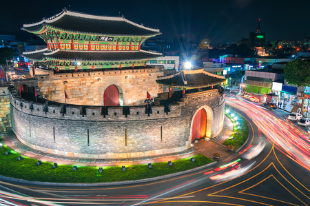 Late night traffic blurs past Paldalmun Gate in Suwon, South Korea. Редакционное