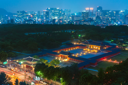 Changgyeonggung Palace lit up at night, with the Seoul skyline in the background.
