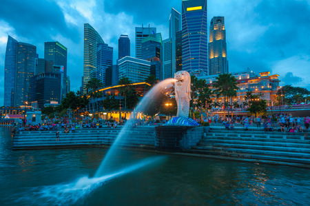 The Merlion fountain lit up against the Singapore skyline at night.