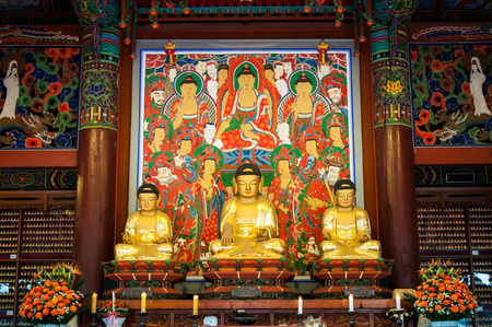 bongeunsa: Three golden Buddhas seated in the lotus position at Bongeunsa Temple in Seoul, South Korea.