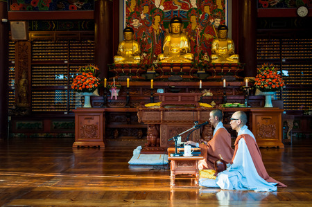 chant: Two Buddhist monks chant prayers at Bongeunsa Temple on October 12, 2014 in Seoul, South Korea. Editorial