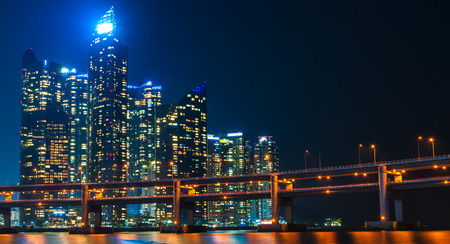 The skyline of Busan lit up at night, with Gwangan Bridge in the foreground. photo