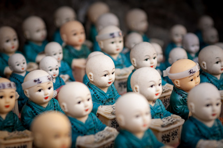 academic achievement: Little figurines scattered around the rocks of Haedong Yonggungsa Temple in Busan, South Korea. The figurines are meant to encourage academic achievement.