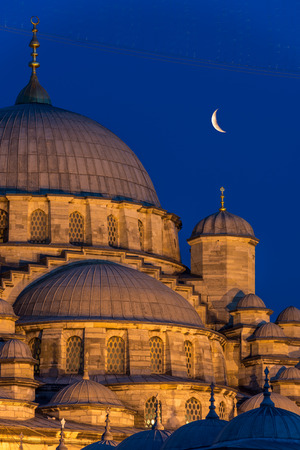 islam moon: A crescent moon hangs over the New Mosque (Yeni Cami) of Istanbul, Turkey.