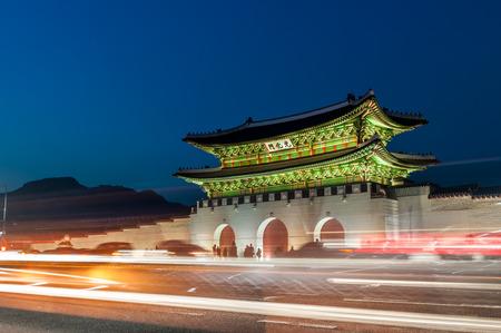 Traffic blurs past Gwanghwamun Gate as evening settles in over Seoul, South Korea.