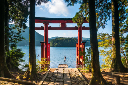 A young woman takes photos with her phone of a torii gate in Hakone, Japan.