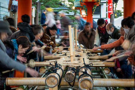 purify: Japanese people purify their hands and mouths with water before entering Fushimi Inari Shrine on New Years Day on January 1, 2015, in Kyoto, Japan.