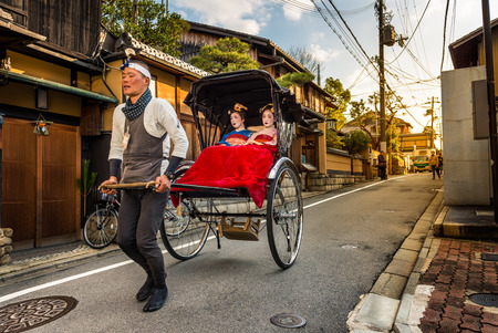 rickshaw: Geishas ride in the back of a rickshaw through the Gion district on December 29, 2015 in Kyoto, Japan. Editorial