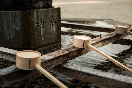purify: Wooden dippers along the chozuya at Heian Shrine in Kyoto, Japan. Worshippers purify their hands and mouths with the water before entering the shrine.