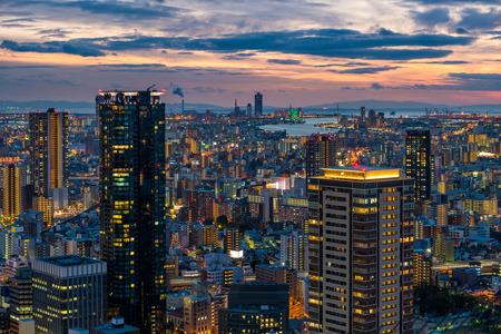 urban sprawl: The sun sets over the vast cityscape of Osaka, Japan.